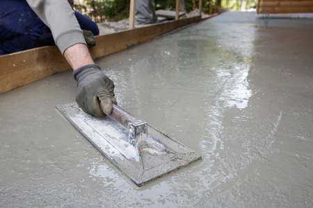 doityourself: Mason leveling and screeding concrete floor base with square trowel in front of the house. Construction business, do-it-yourself, precision work around the house concept.