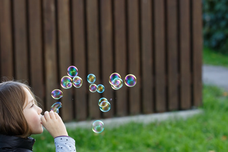 Little girl blowing bubbles, having fun, enjoying carefree childhood. Youth, fun and children games concept with copy space.