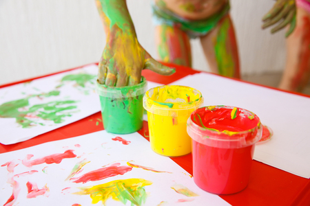 Child dipping fingers in washable, non-toxic finger paints, painting a drawing. Creativity, sensory play, innovative learning, fun childhood concept.