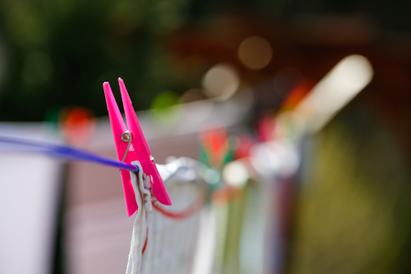 Clothespins holding laundry on the drying line, drying clothes outside on fresh air, wind and sun. Housework, family life, household, natural living and lifestyle concept.