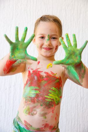 finger paint: Little girl showing her hands, covered in finger paint after painting a picture and her body with it. Sensory play, permissive upbringing, fun childhood concept, selective sharpness. Stock Photo