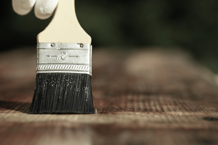 doityourself: Paintbrush sliding over wooden surface, protecting wood for exterior influences, weathering, insects and fungus. Carpentry, woodwork, home improvement, do-it-yourself concept with copy space.