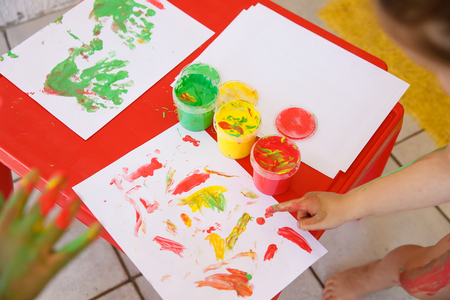 Children painting a drawing with finger paints, used for finger drawing and sensory play. Fun childhood, sensory and experience-based learning concept. Stock Photo