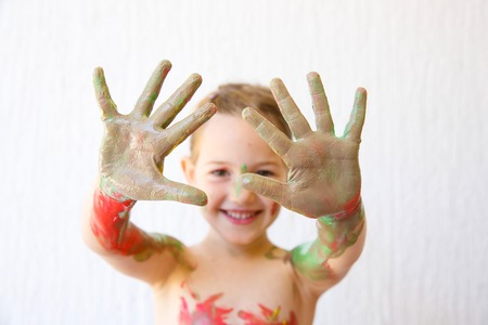 sharpness: Little girl showing her hands, covered in finger paint after painting a picture and her body with it. Sensory play, permissive upbringing, fun childhood concept, selective sharpness. Stock Photo