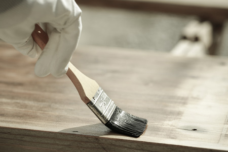 doityourself: Carpenter holding a paintbrush over wooden surface, protecting wood for exterior influences and weathering. Carpentry, wood treatment, hard at work, home improvement, do-it-yourself concept. Stock Photo