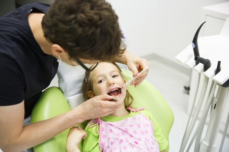 dental fear: Child patient sitting on dental chair in paediatric dentists office on her regular checkup for caries and gum disease. Early prevention, oral hygiene and milk teeth care concept. Stock Photo