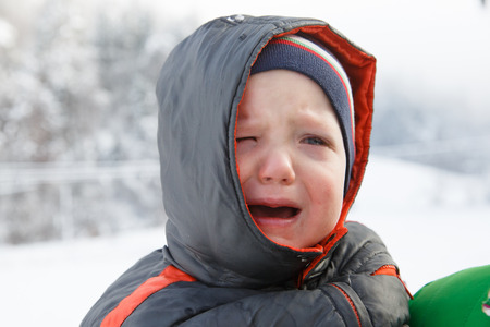 Little boy crying, not wanting to walk outside in the winter landscape. Temper tantrum, distress and emotional outburst concept.