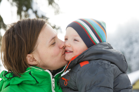 having fun in winter time: Mother kissing her son in a snowy winter landscape, bonding, having fun, smiling, talking and enjoying family time. Mothers day, family values, parents love and happy childhood concept.