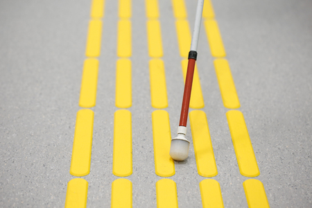 detecting: Blind pedestrian walking and detecting markings on tactile paving with textured ground surface indicators for blind and visually impaired. Blindness aid, visual impairment, independent life concept. Stock Photo