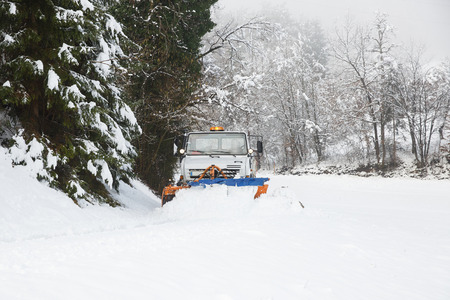snow  snowy: Snow plough making its way through the snowy country road, clearing it of snow after blizzard. Professional winter services, road conditions in winter concept. Stock Photo