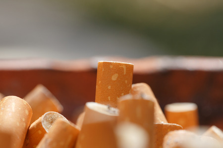 Close-up of big pile of put out cigarettes in an ashtray. Smoking, smoker, addiction, health hazard, lung cancer concept.
