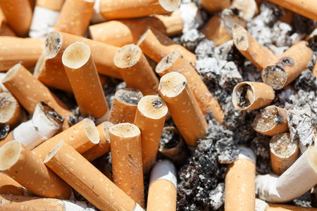 crave: Big pile of put out cigarettes in an ashtray. Smoking, smoker, addiction, health hazard, lung cancer concept.