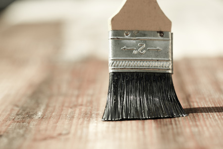 doityourself: Paintbrush sliding over wooden surface, protecting wood for exterior influences, weathering, insects and fungus. Carpentry, woodwork, home improvement, do-it-yourself concept with copy space.   Stock Photo
