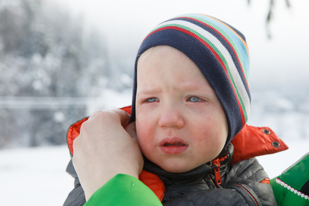 Little boy crying, his mother trying to console him in a winter landscape. Temper tantrum, distress and emotional outburst concept.