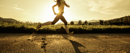 Fit woman running fast, training in bright sunshine Imagens