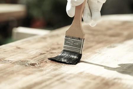 Gloved hand holding a paintbrush over wooden surface, protecting wood for exterior influences and weathering. Carpentry, wood treatment, hard at work, home improvement, do-it-yourself concept.