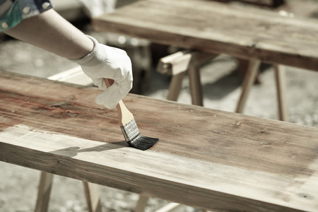 Painting wood with wood protection paint for weathering, fungus and insects on sawhorses. Outdoor protection, carpentry, hard at work, home improvement, do-it-yourself concept. 版權商用圖片