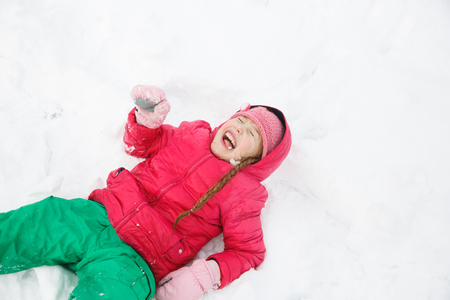 Playful girl with braids playing in snow, snow diving, having fun and being active. Natural lifestyle and free childhood concept with copy space. Stock Photo