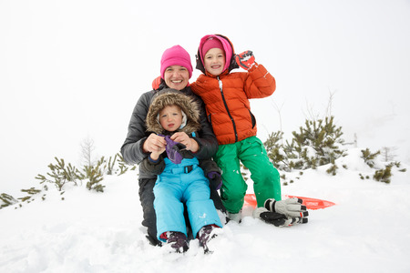 Mother with daughter and son, together in a snowy winter landscape, bonding, having fun, smiling, and enjoying family time. Mothers day, family values, parents love and happy childhood concept.