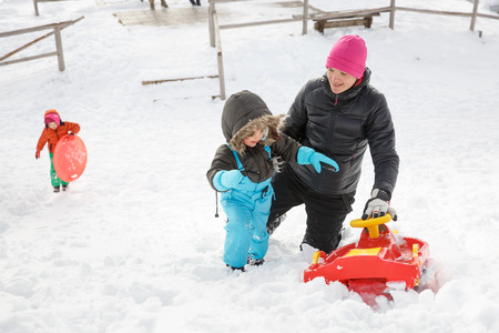 having fun in winter time: Mother with son snow sledding and daughter with saucer sled in the background, in snowy winter landscape, having fun and enjoying family time. Family values, parents love and happy childhood concept.   Stock Photo