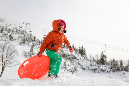 kids at the ski lift: Beautiful girl, enjoying winter and snow, playing with plastic saucer sled, ski lifts in the back. Active family lifestyle, outdoor and natural childhood, carefree childhood concept.