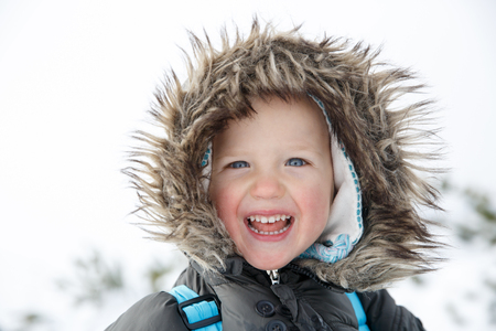 Blue eyed little boy in a winter landscape, dressed in warm clothes, enjoying the snow, smiling. Active family lifestyle, outdoor and natural childhood, happy, carefree child concept.