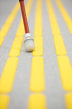 impaired: Blind pedestrian walking and detecting markings on tactile paving with textured ground surface indicators for blind and visually impaired. Blindness aid, visual impairment, independent life concept.