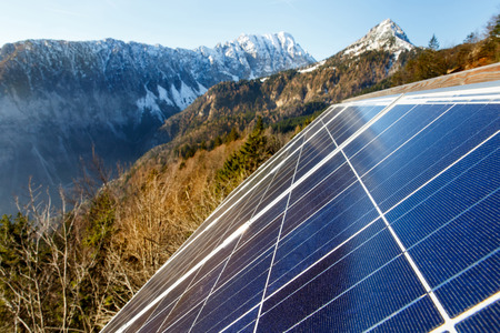 sustainable resources: Closeup of photovoltaic solar panels in mountainous natural area, gathering sunlight. Sustainable resources, environmental conservation, alternative power source and generation, green energy concept.   Stock Photo