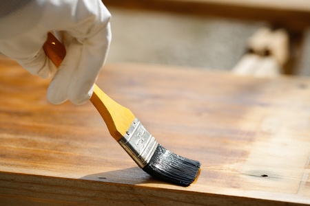 doityourself: Gloved hand holding a paintbrush over wooden surface, protecting wood for exterior influences and weathering. Carpentry, wood treatment, hard at work, home improvement, do-it-yourself concept.   Stock Photo