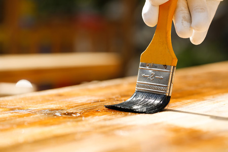 Gloved hand holding a paintbrush over wooden surface, protecting wood for exterior influences and weathering. Carpentry, wood treatment, hard at work, home improvement, do-it-yourself concept.   Stock Photo