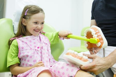 치과 의사의 자에 웃는 소녀, 그녀의 소아 치과 의사에 의해 적절한 치아 칫솔질에 대한 교육된다. 조기 예방, 육아에 대한 인식, 구강 위생 시범 개념 스톡 콘텐츠