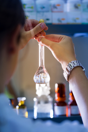 Professional woman, laboratory technician working in a medical lab with round-bottom flask. Medicine, healthcare, laboratory equipment, science concept.