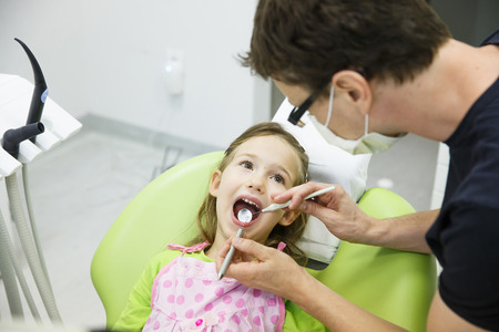 unease: Child patient sitting on dental chair in paediatric dentists office on her regular checkup for caries and gum disease. Early prevention, oral hygiene and milk teeth care concept.