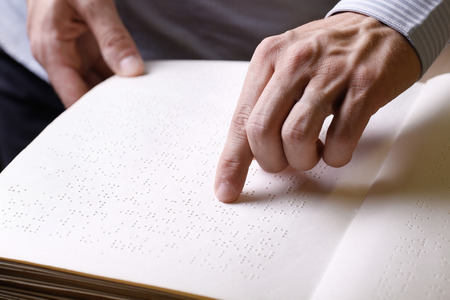 Blind person touching book, written in braille writing, reading it. Blindness aid, visual impairment, independent life concept.