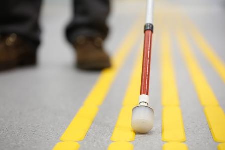 Ciega a pie de peatones y la detección de marcas en pavimentos táctiles con indicadores de superficie con textura del suelo para ciegos y deficientes visuales. ayuda ceguera, discapacidad visual, el concepto de vida independiente. Foto de archivo - 69374918