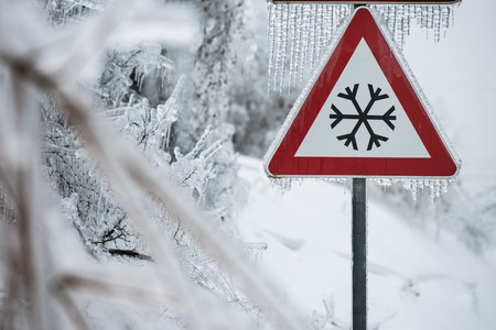 driving conditions: Traffic sign for icy road with sleet covered trees. Danger on the road, black ice danger, wintertime concept.