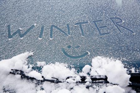 """눈 덮인 자동차 앞 유리에 그린 """"겨울""""과 재밌는 단어. 겨울, 재미, 날씨 및 감기 개념. 스톡 콘텐츠"""