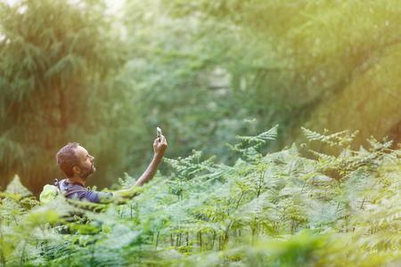 Wandelaar die een signaal van een mobiele telefoon zoekt, verdwaalt in het weelderige bos, verlicht door glanzend gouden zonlicht. Actieve levensstijl, modern leven, technologische afhankelijkheid en wildernisconcept en kopieerruimte.