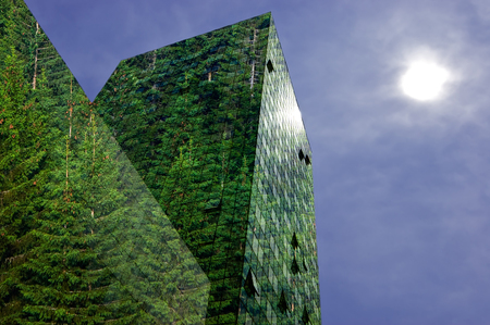 Green, renewable energy in the city: modern building covered with spruce forest. Sustainable energy, pollution and urbanity concept with copy space.