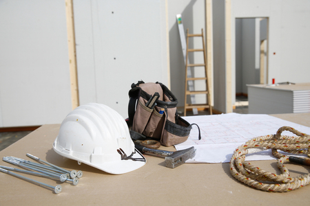 libel: Building equipment, hardware and building plan: helmet, hammer, rope, screws, workers tool bag. Construction industry, diy, carpentry and hard at work concept.