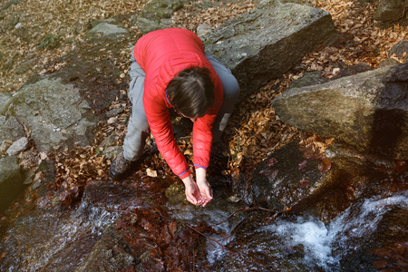 Thirsty hiker drinking water from a crystal clear stream in the mountains. Adventure, fundamental right to water, back to nature and natural lifestyle concept.