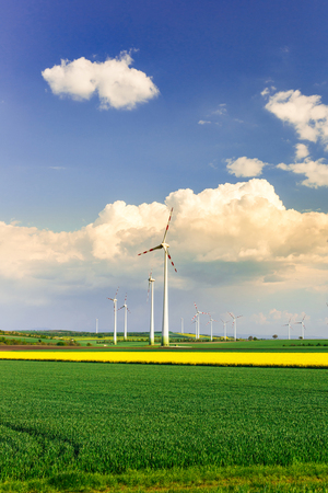 Wind farm with spinning wind turbines amidst agricultural land of intensive crop production. Sustainable and renewable power production, ecology and environmental conservation concept.