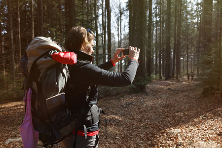 authentic: Hiker taking photographs on her hike through the woods. Memory collection, active lifestyle, mobile phone dependency concept.   Stock Photo