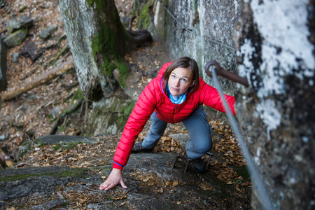 Woman climbing rock in the forest, holding security railing, ascending to the top, succeeding. Active lifestyle, progress and improvement, conquering challenges concept.