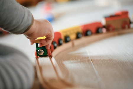 Child playing with wooden train toys. Educational and natural toys, learning through experience concept, creative playing, gross and fine motor skills, educational approach concept. Foto de archivo