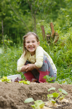 Little girl having fun in the garden, planting, gardening, helping her mother. Happy, natural childhood concept.  Stock Photo