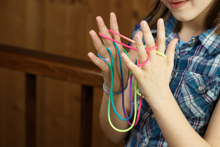 Child playing classic, old-school string game and didactic toy with her fingers, making cats cradle, developing her motor skills. IQ, education, intelligence, fun and childhood concept. Stock Photo