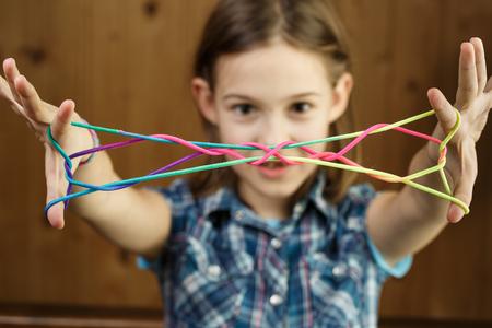 Kind spielt klassisches Saitenspiel der alten Schule und didaktisches Spielzeug mit den Fingern, schafft die Form der Jakobsleiter und entwickelt seine motorischen Fähigkeiten. IQ, Bildung, Intelligenz, Spaß und Kindheitskonzept.