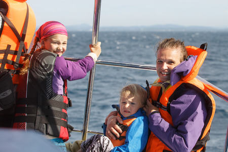 Family on a blue whale watching trip. Smiling girl in safety jacket on a boat trip. Mother holding baby.