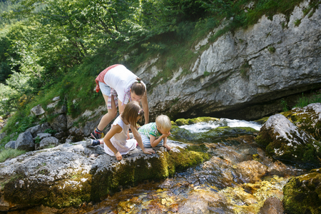 Mother with kids drinking water from a pure, fresh and cool mountain stream on a family trip. Outdoor lifestyle, natural parenting, childhood experience concept.